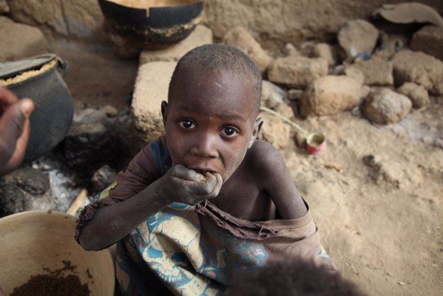 Un Niño Maliense Comiendo Restos De Comida Para El Ganado