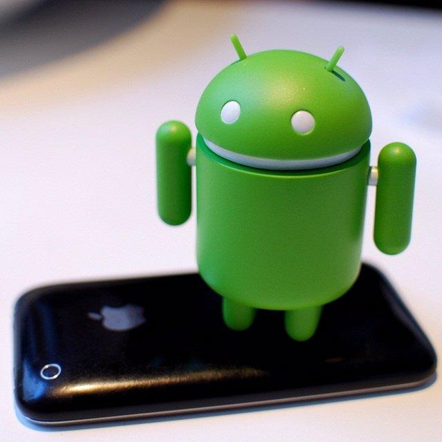 Muñeco Android sobre un iPhone 3G
