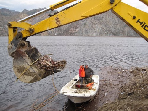 Operarios retiran restos en los márgenes del río