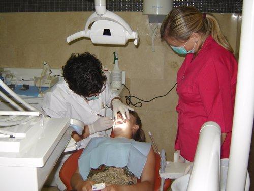 Una Médico Dentista Revisa La Boca De Una Paciente