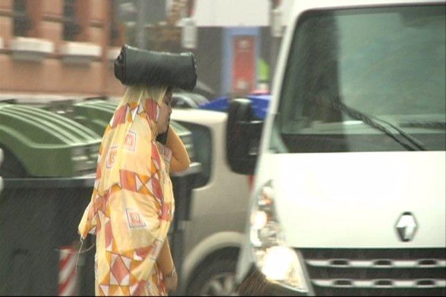 Una mujer se resguarda de la lluvia como puede