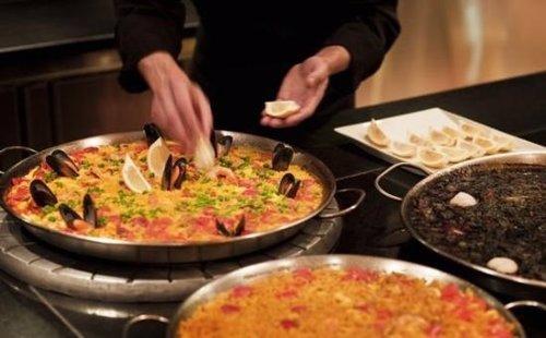 Cocinero cocinando una paella. Comida/Cena