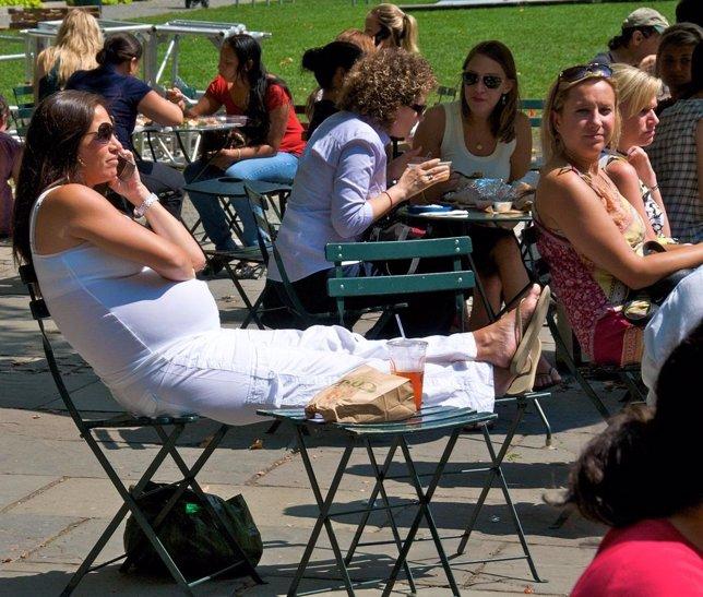 Embarazada comiendo en un parque