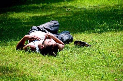 Chico tumbado en el césped con una botella de alcohol