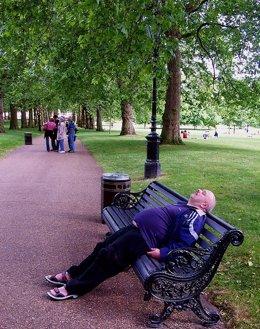 Hombre cansado con barriga tumbado en un banco de un parque
