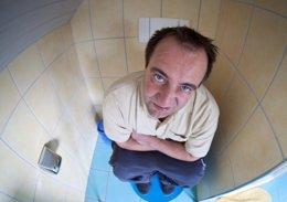 Hombre con hemorroides en el baño