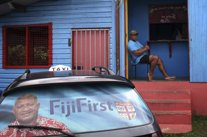 Election poster for Bainimarama can be seen in the rear window of a taxi as a ma