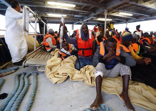 Inmigrantes ilegales siendo atendidos por efectivos sanitarios en alta mar.