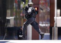 Policía corre hacia la cafetería de Sydney donde se encuentra los rehenes