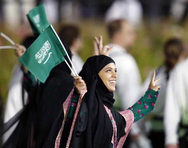 Una mujer saudí sosteniendo la bandera de su país