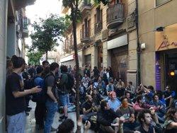 Uns 50 activistes se senten davant del cordó policial prop del 'Banc Expropiat' (EUROPA PRESS)