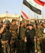 Foto: El primer ministro de Irak iza la bandera del país en Faluya tras la expulsión del Estado Islámico