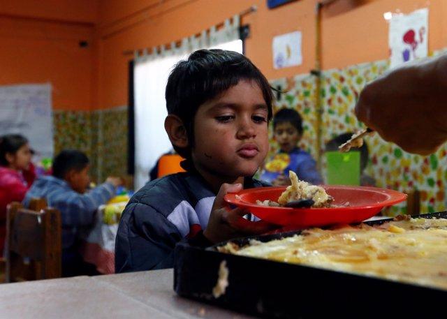 Niño recibe comida en el centro 'Che Pibe' en Villa Fiorito, Buenos Aires