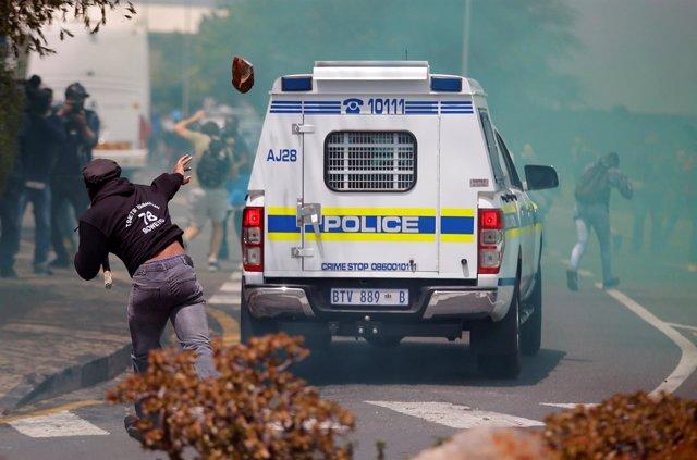 Un manifestante apedrea un coche de Policía en las protestas universitarias