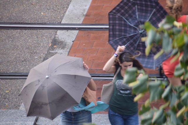 Unas ciudadanas intentan controlar sus paraguas, este martes en Zaragoza.