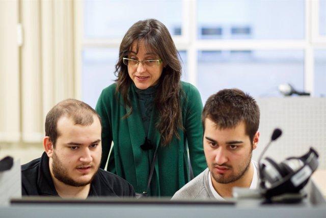 La profesora de inglés Nieves Candela Osés atiende a dos estudiantes.