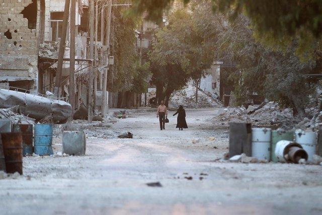Civiles pasean entre edificios derruidos en un barrio rebelde de Alepo