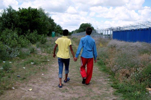 Menores refugiados caminan junto a la valla fronteriza en Serbia