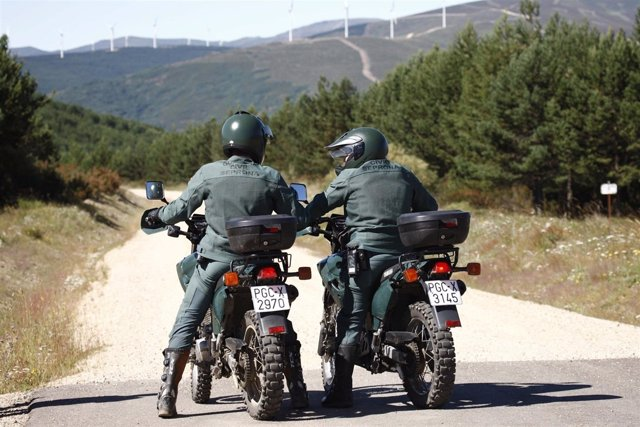 Agentes de la Guardia Civil de espaldas en moto