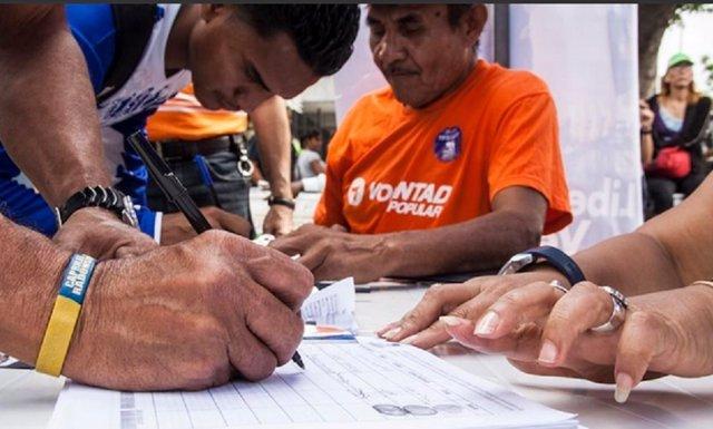 Venezolanos firmando