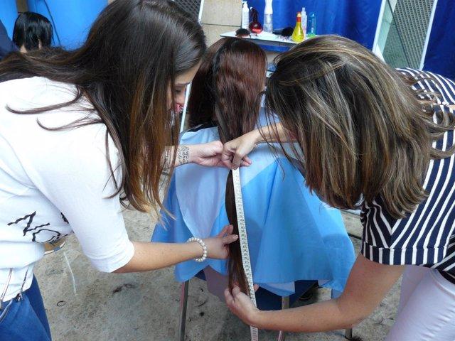 Corte de pelo solidario en el Hospital de La Ribera, en Alzira (Valencia)