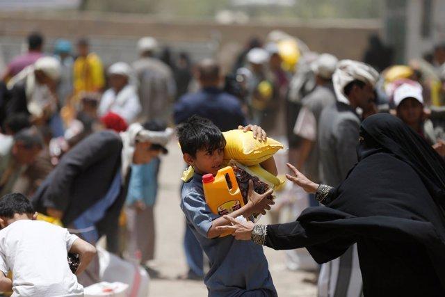 Niño carga comida en Yemen