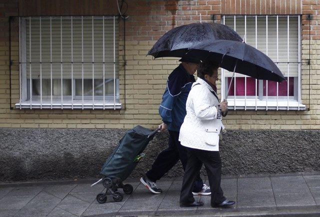 Gente con paraguas bajo la lluvia.