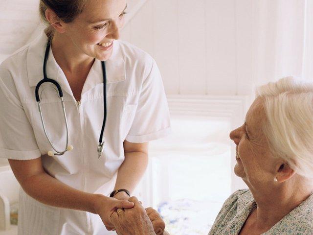 Consulta médica. Enfermeta atiende a una anciana. Médico