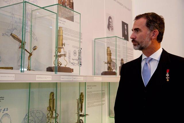 Felipe VI observando uno de los microscopios de la exposición