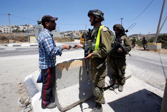 Un militar israelí pide la documentación a un palestino en Cisjordania.