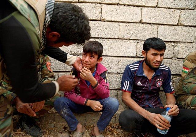 Un niño iraquí habla con un miliciado kurdo tras escapar de zona de ISIS