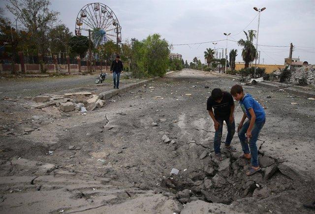 Niños inspeccionan el suelo destrozado después de un bombardeo en Guta