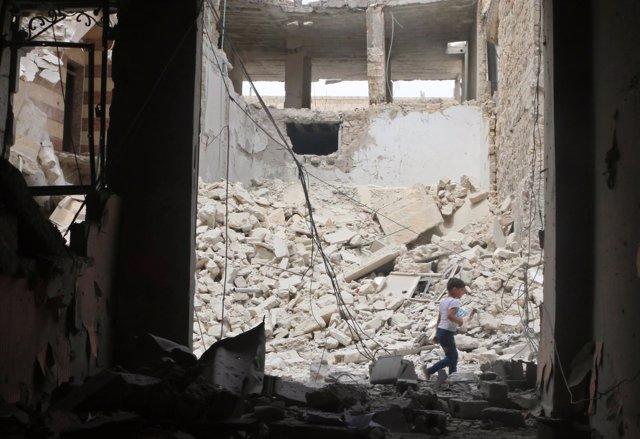 Un niño camina entre escombros tras un bombardeo aéreo en Alepo