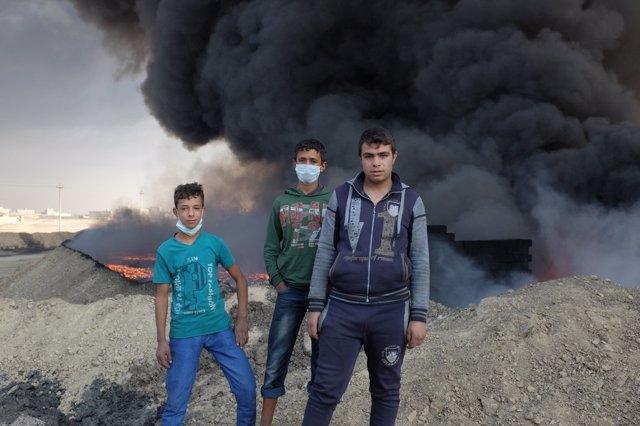 Varios niños juegan junto a una nube de humo en Qayara, Irak.