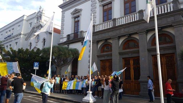 Izado de la bandera de siete estrellas verdes frente al Ayuntamiento