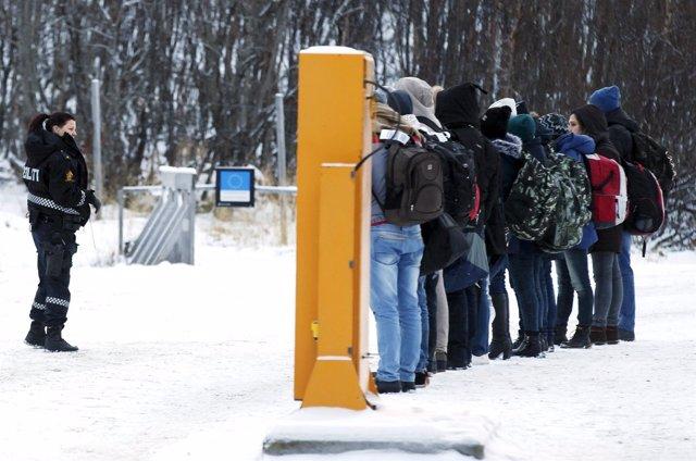 Migrantes reciben órdenes de Policía de Noruega en puesto fronterizo