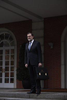 Rajoy con su cartera a su llegada a la Moncloa