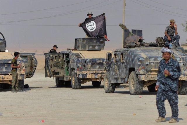 Militares iraquíes posan con la bandera de Estado Islámico