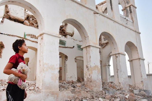 Niño junto a una casa destruida en Adén