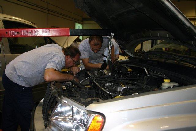 Dos hombres revisan un coche en un taller
