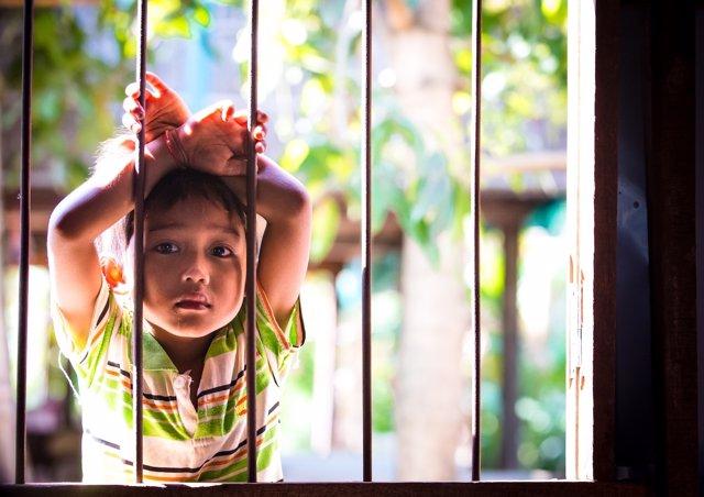 Niño tras una reja