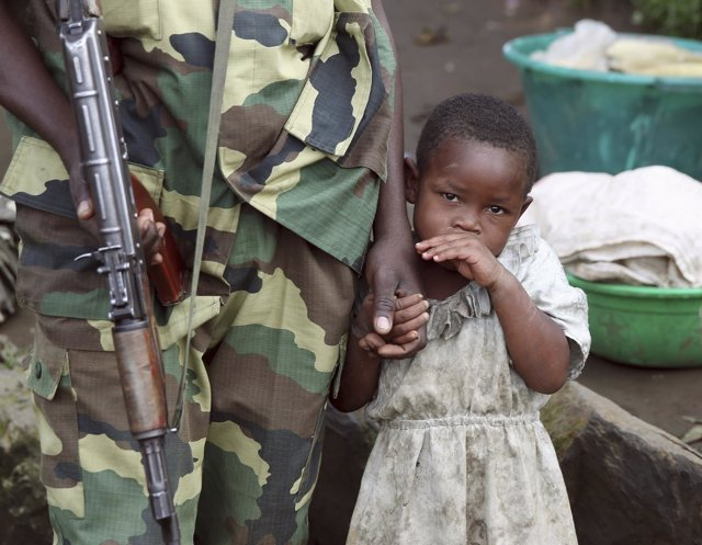 Una niña junto a un soldado del M-23
