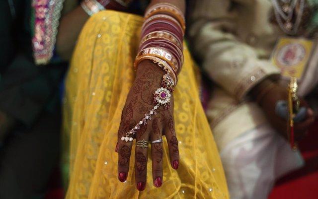 Una mano decorada con henna y joyería durante una boda en India