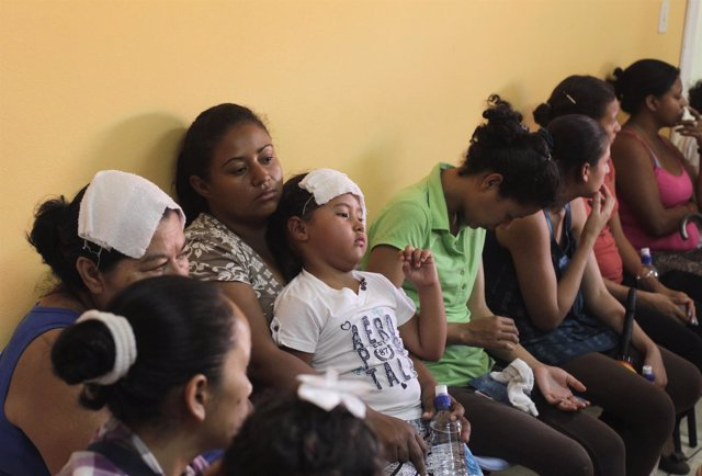 mujeres y niños esperando en una consulta médica para ser atendidos.