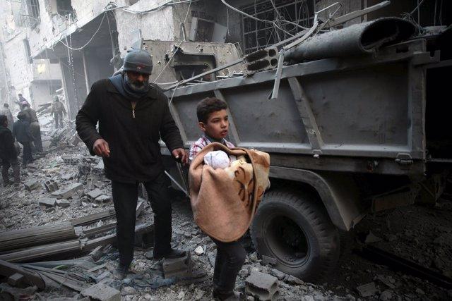 Un niño con un bebé tras un bombardeo en Duma, alrededores de Damasco