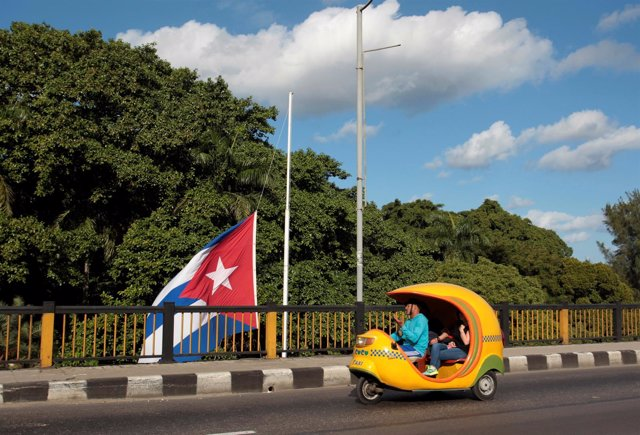 Un cocotaxi y la bandera cubana a media asta por la muerte de Fidel Castro