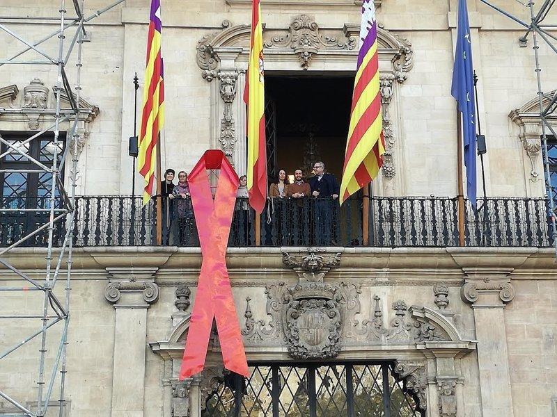 El Ayuntamiento de Palma cuelga un lazo rojo en su fachada para adherirse al Día Mundial de la Lucha contra el Sida