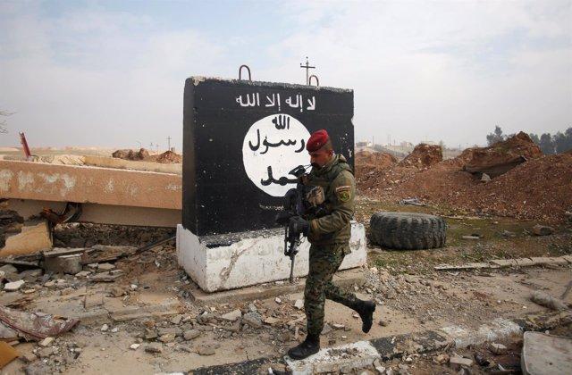 Un soldado iraquí pasa al lado de una bandera del Estado Islámico en Mosul