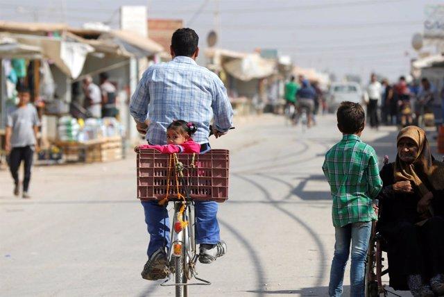 Un refugiado sirio con su hija en un campo de refugiados en Jordania
