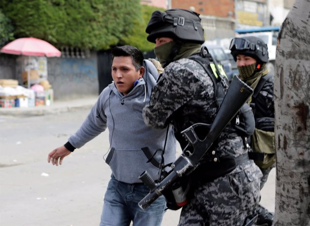 A coca grower from Yungas is arrested by riot policemen during clashes in La Paz